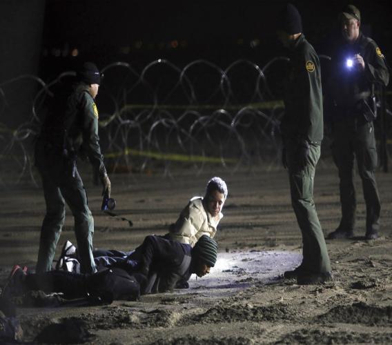 U.S. Border Patrol detain Honduran migrants after they walked onto U.S. territory from Tijuana, Mexico. (AP Photo/Felix Marquez, File)