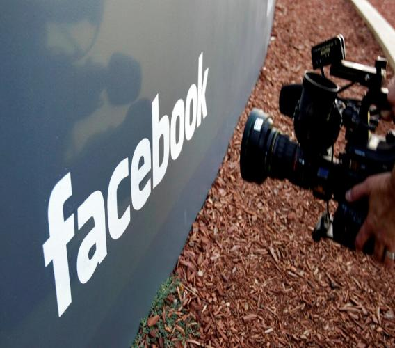 In this May 18, 2012, file photo a television photographer shoots the sign outside of Facebook headquarters in Menlo Park, Calif. (AP Photo/Paul Sakuma, File)