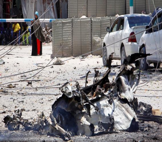 A woman stands behind wreckage left from a suicide car bomb attack on a government building in the capital Mogadishu, Somalia Saturday, March 23, 2019. (AP Photo/Farah Abdi Warsameh)