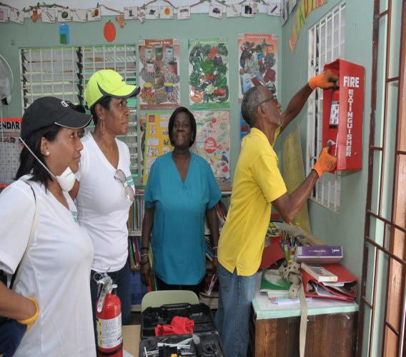 Fire Alarm Technician from National Supply Limited, Eaton McKoy replaces a fire extinguisher at the schoolhouse at the Strathmore Children's Home in Spanish Town, St Catherine. Looking on are Supreme Ventures Limited Chief Marketing Officer, Heather Goldson (far left); President and CEO, Ann-Dawn Young Sang and house mother, Marcia Tucker.