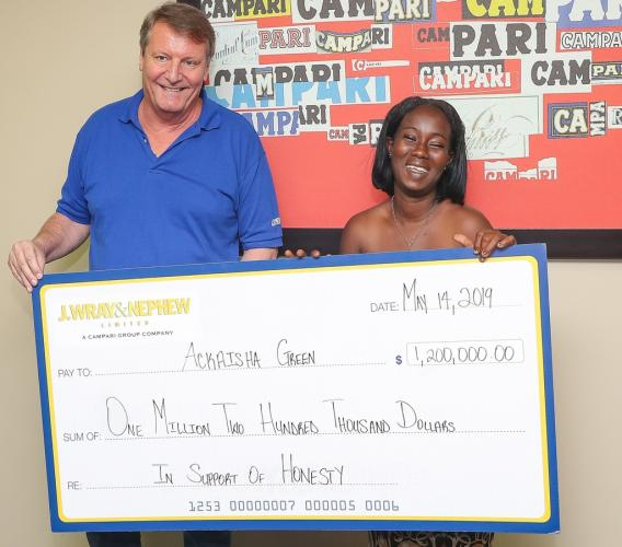 J. Wray & Nephew (JWN) Limited's Managing Director, Jean-Philippe Beyer (left), shares a joyous moment with Ackaisha Green, after making a presentation of $1.2 million for honesty at JWN's corporate offices in New Kingston. (Photo: Leo Hudson)
