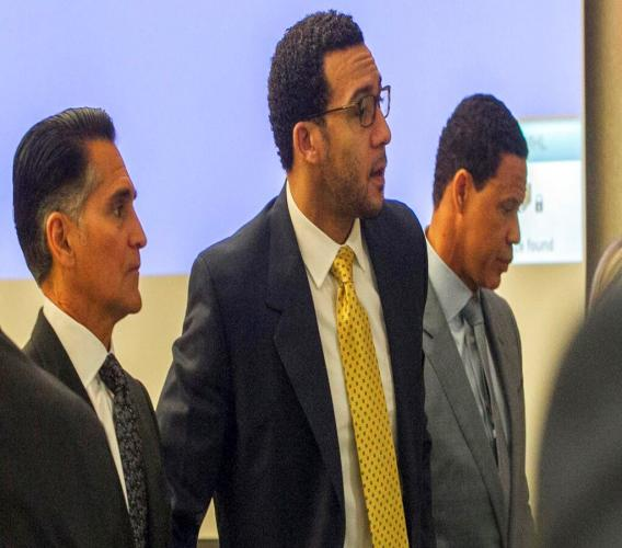 Former NFL football player Kellen Winslow Jr., centre, stands as the jury enters the courtroom on the first day of his rape trial, Monday, May 20, 2019, in Vista, Calif. Winslow's attorneys Brian Watkins, right, and Marc Carlo, left, flank him. (John Gibbins/The San Diego Union-Tribune via AP, Pool)