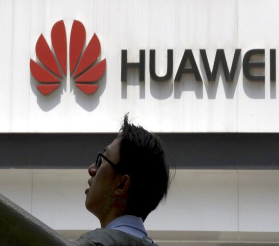 In this photo taken Thursday, May 16, 2019, a man past by a Huawei store in Beijing.  (AP Photo/Ng Han Guan)