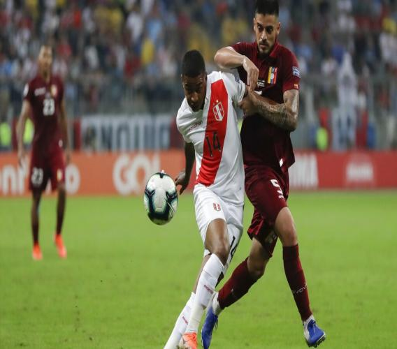 Peru's Andy Polo, left, vies for the ball with Venezuela's Junior Moreno, right, during a Copa America Group A soccer match at the Arena do Gremio stadium in Porto Alegre, Brazil, Saturday, June 15, 2019. (AP Photo/Andre Penner)