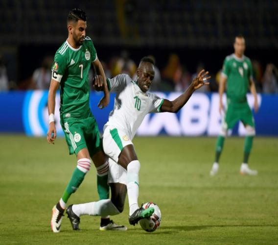 L'attaquant algérien Riyad Mahrez (g) à la lutte avec celui du Sénégal lors de la CAN-2019 , le 27 juin 2019 au Caire