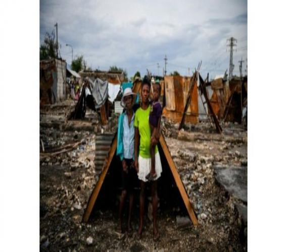 (g-d): Iris Daniel, Lovely Saint-Pierre et Evanston Daniel près de la hutte qui leur sert de refuge précaire dans leur quartier incendié par des gangs, le 1er juillet 2019 à Port-au-Prince, en Haïti ((c) Afp)