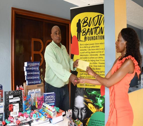 Patrick Newman, facility administrator at Mount Olivet Boys' Home, hands a thank you letter to Rosemary Duncan, director at the Buju Banton Foundation, at a presentation ceremony last Saturday.