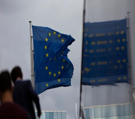 European Union flags flap in the wind as two people walk up a set of stairs outside EU headquarters in Brussels, Sunday, Oct. 13, 2019. Technical talks on Brexit continued in Brussels over the weekend with European Union Brexit negotiator Michel Barnier due to brief EU ambassadors. (AP Photo/Virginia Mayo)