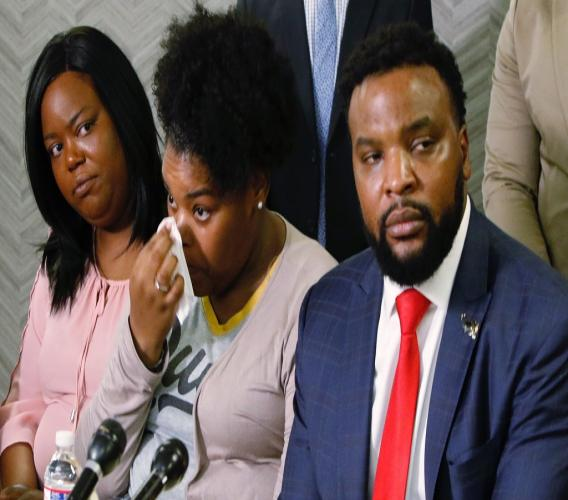 Amber Carr, center, wipes a tear as her sister, Ashley Carr, left, and attorney Lee Merritt, right, listen to their brother Adarius Carr talk about their sister, Atatiana Jefferson during a news conference Monday, Oct. 14, 2019 in downtown Dallas. (Irwin Thompson/The Dallas Morning News via AP)