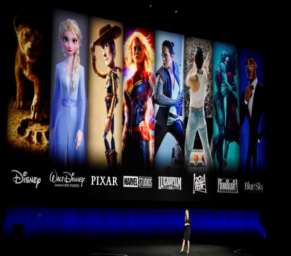 In this April 3, 2019, file photo characters from Disney and Fox movies are displayed behind Cathleen Taff, president of distribution, franchise management, business and audience insight for Walt Disney Studios during the Walt Disney Studios Motion Pictures presentation at CinemaCon 2019, the official convention of the National Association of Theatre Owners (NATO) at Caesars Palace in Las Vegas. On Tuesday, Nov. 12, Disney Plus launches its streaming service. (Photo by Chris Pizzello/Invision/AP, File)