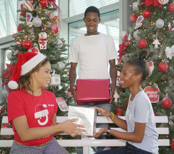 (L-R) Ayanna Kirton, Brand Marketing Manager at Digicel Jamaica, shares more this Christmas with customers Sedayne Samuels and Mockalea Gordon, shortly after the launch of the Digicel 'Shake To Win' Christmas promotion.