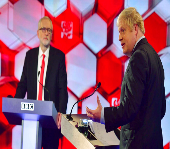 Opposition Labour Party leader Jeremy Corbyn, left, and Britain's Prime Minister Boris Johnson, during a head to head live Election Debate at the BBC TV studios in Maidstone, England, December 6, 2019. Britain's Brexit is one of the main issues for political parties and for voters, as the UK prepares for a General Election on December 12. The debate is moderated by TV presenter Nick Robinson, right. ( Jeff Overs/BBC via AP)