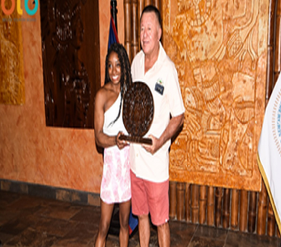 Minister of Tourism and Civil Aviation Manuel Heredia presented a wooden carving of the Coat of Arms to Simone Biles.