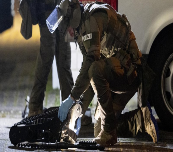 A special forces officer works on a robot in front of a house that is searched through by police in Hanau, Germany Thursday, Feb. 20, 2020. Eight people were killed in shootings in and outside two hookah lounges in a southwestern German city late Wednesday, and authorities were searching for the perpetrators. (AP Photo/Michael Probst)
