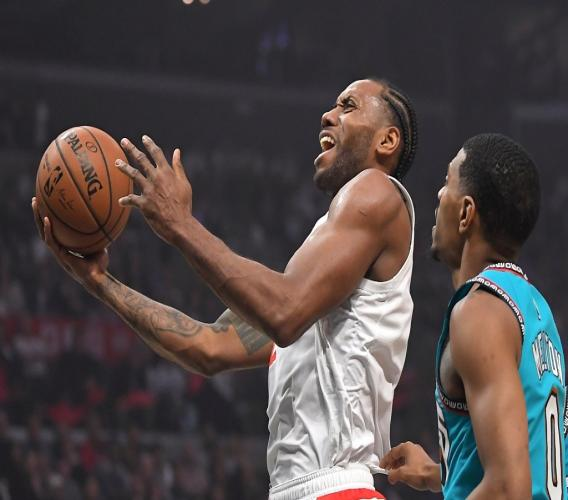 Los Angeles Clippers forward Kawhi Leonard, left, shoots as Memphis Grizzlies guard De'Anthony Melton defends during the first half of an NBA basketball game Monday, Feb. 24, 2020, in Los Angeles. (AP Photo/Mark J. Terrill).