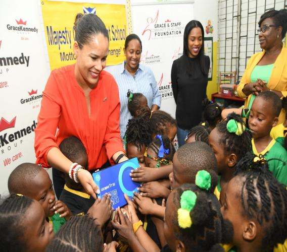 Gail Moss-Solomon General Counsel & Chief Corporate Secretary, GraceKennedy Limited (GKL), allowing children of Majesty Gardens Infant School to get close to one of ten tablets, which she presented to the School on February 21.