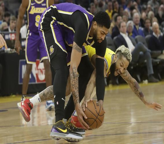 Golden State Warriors guard Ky Bowman, bottom, reaches for the ball under Los Angeles Lakers forward Anthony Davis during the first half of an NBA basketball game in San Francisco, Thursday, Feb. 27, 2020. (AP Photo/Jeff Chiu).