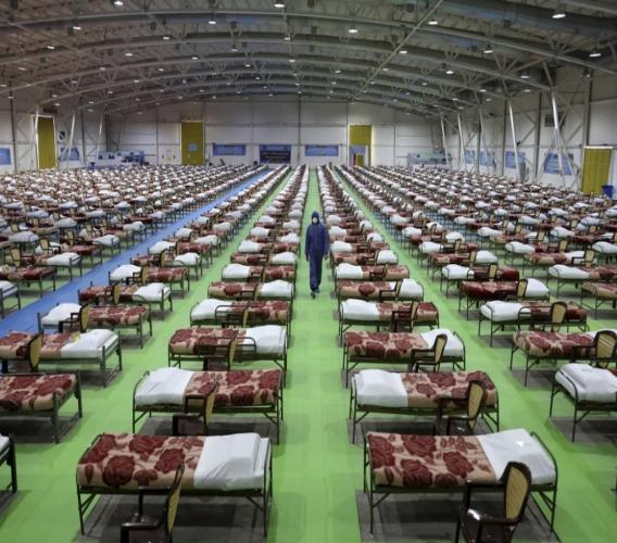A member of the Iranian army walks past rows of beds at a temporary 2,000-bed hospital for COVID-19 coronavirus patients set up by the army at the international exhibition center in northern Tehran, Iran. (AP Photo/Ebrahim Noroozi)