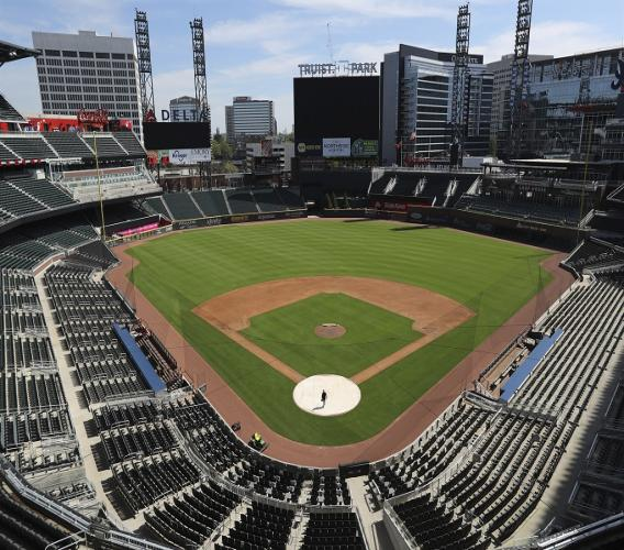 In this April 1, 2020, file photo, Atlanta Braves field manager Tyler Lenz walks across the covered home plate at Truist Park in Atlanta. (Curtis Compton/Atlanta Journal-Constitution via AP, File).
