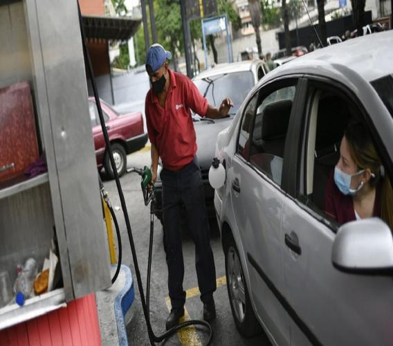 A worker wearing a face mask amid the new coronavirus pandemic works to fill up a client's gas tank at a PDVSA state oil company gas station in Caracas, Venezuela, Monday, May 25, 2020. The first of five tankers loaded with gasoline sent from Iran this week is expected to temporarily ease Venezuela's fuel crunch while defying Trump administration sanctions targeting the two U.S. foes. (AP Photo/Matias Delacroix)