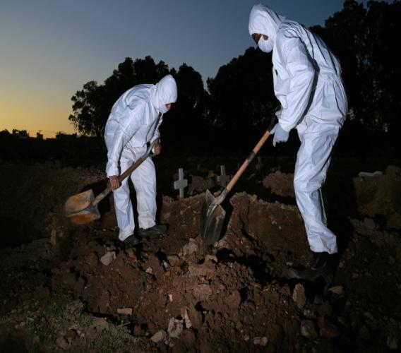 Des employés d'un cimetière en combinaison de protection enterrent une victime du coronavirus, le 29 mai 2020 à Rio de Janeiro