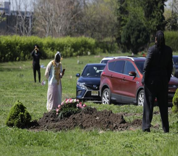 Family and friends watch from a distance or their cars as Erika Bermudez stands over her mother Eudiana Smith's grave after she was buried in Bayview Cemetery, Saturday, May 2, 2020 in Jersey City, N.J. Bermudez was not allowed to approach the gravesite until after cemetery workers had buried her mother completely; other members of the family and friends stayed in their cars. (AP Photo/Seth Wenig)