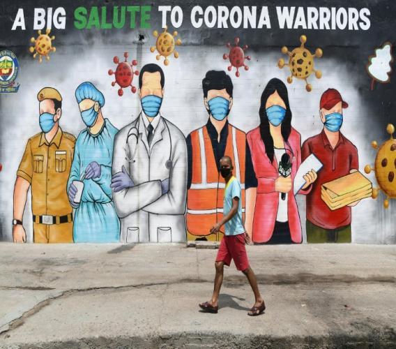"""Un homme passe dant une fresque murale qui rend hommage aux """"guerriers du corona"""", le 31 mai à New Delhi"""