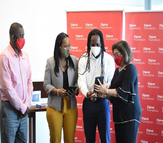 (From left) Digicel Jamaica chairman Harry Smith; Acting Chief Education Officer Dr Kasan Troupe; State Minister in the Education Ministry Alando Terrelonge; and Digicel Foundation chair Jean Lowrie Chin examine one of the tablets. (Photos: Marlon Reid)