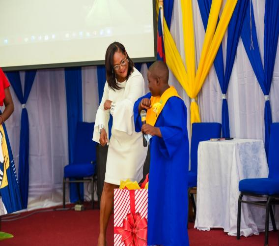 Nina Peters, Business Relationship and Sales Manager, JN Bank, smiles as she extends a socially distant greeting to graduate Andwele Haye, after he presented her with a thank you gift for her presentation at the Hague Primary & Infant School graduation at the   First Assembly Church in Falmouth, Trelawny.