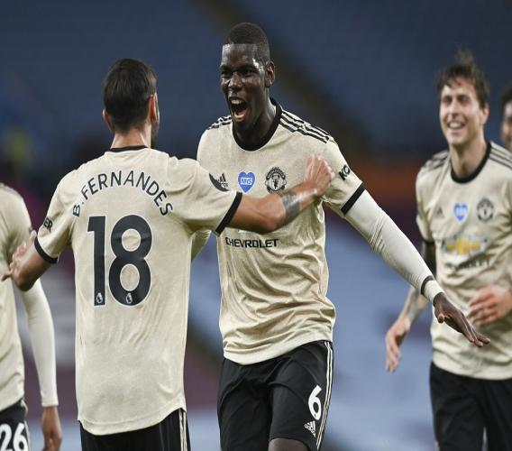 Manchester United's Paul Pogba celebrates with teammate Bruno Fernandes, left, after scoring his team's third goal during the English Premier League football match against Aston Villa at Villa Park in Birmingham, England, Thursday, July 9, 2020. (AP Photo/Shaun Botterill,Pool).