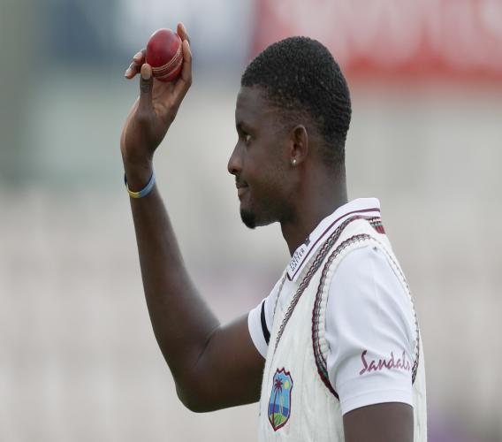 West Indies' captain Jason Holder holds up the ball as he leaves the field after taking six wickets during the second day of the first cricket Test match against England at the Ageas Bowl in Southampton, England, Thursday, July 9, 2020 (Adrian Dennis/Pool via AP).