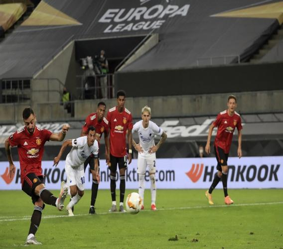 Manchester United's Bruno Fernandes scores his sides first goal from a penalty kick during the UEFA Europa League quarterfinal match between Manchester United and FC Copenhagen in Cologne, Germany, Monday, Aug. 10, 2020. (Wolfgang Rattay/Pool via AP)