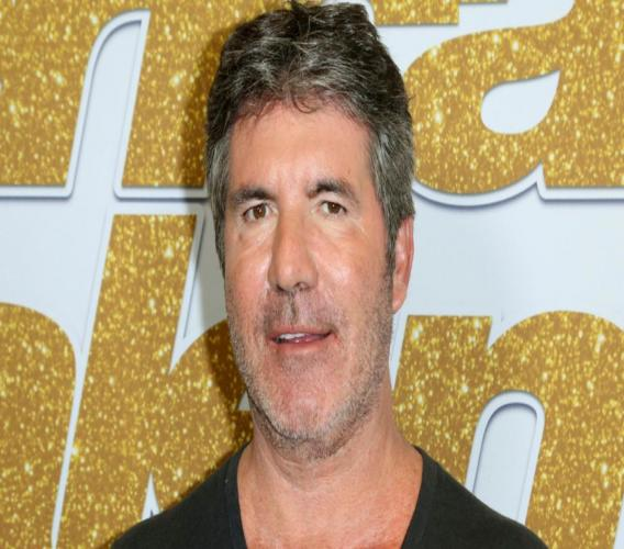 """In this Aug. 28, 2018, file photo, Simon Cowell arrives at the """"America's Got Talent"""" Season 13 Week 3 red carpet at the Dolby Theatre in Los Angeles. Cowell broke his back Saturday, Aug. 8, 2020, while testing his new electric bicycle at his home in California. (Photo by Willy Sanjuan/Invision/AP, File)"""