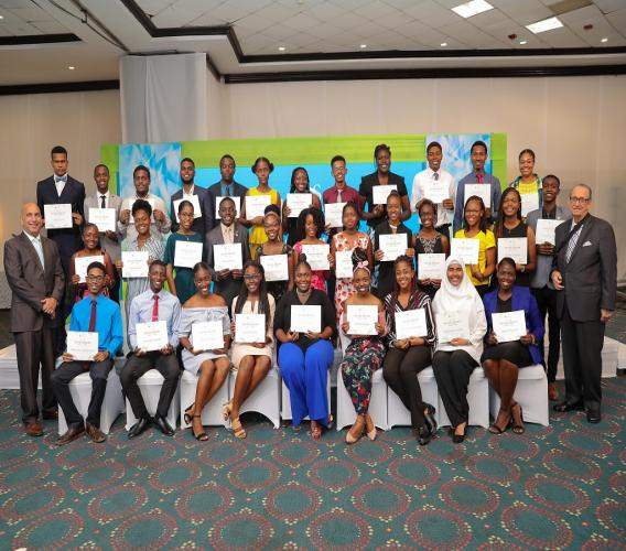 The 2019 cohort of the Sagicor Foundation tertiary scholarship awardees are photographed with Christopher Zacca (left), President and CEO, Sagicor Group Jamaica and R Danny Williams (right), Chairman of the Sagicor Foundation, at last year's Sagicor Foundation Scholarship Awards Ceremony held at the Jamaica Pegasus Hotel.