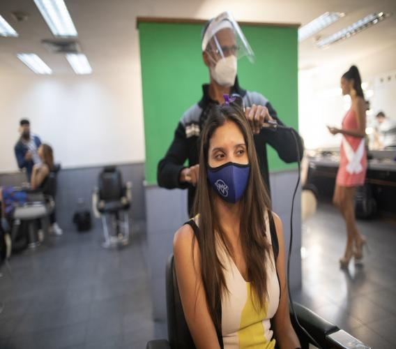 A beauty pageant contestant, wearing a protective face mask issued by the Miss Venezuela beauty pageant, watches as her hair is styled in a Venevision television station dressing room, in Caracas, Venezuela, Friday, September 18, 2020. Quarantine rules and social distancing has forced the contestants to train at home and online with limited access to the venue itself where strict measures are in place. The pageant is due to take place on September 24. (AP Photo/Ariana Cubillos)