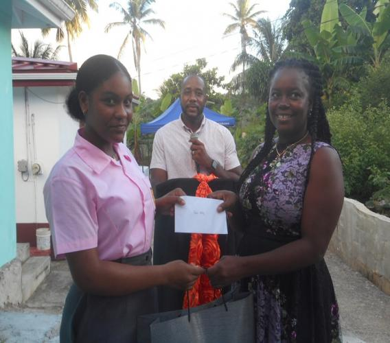 A student of the Vieux-Fort Comprehensive Secondary School (left) receiving her cheque and school supplies
