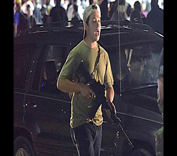 In this Tuesday, August 25, 2020 file photo, Kyle Rittenhouse carries a weapon as he walks along Sheridan Road in Kenosha, Wis., during a night of unrest following the weekend police shooting of Jacob Blake. . (Adam Rogan/The Journal Times via AP, File)