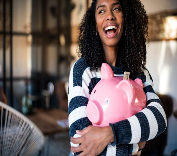 iStock photo of a woman hugging her piggy bank.