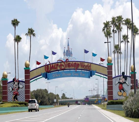 In this Thursday, July 2, 2020, file photo, cars drive under a sign greeting visitors near the entrance to Walt Disney World, in Lake Buena Vista, Florida. Photo: AP Photo/John Raoux/ File)