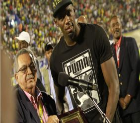 Victor Lopez, president of the North American, Central American and Caribbean Athletic Association (left) makes a presentation to Usain Bolt on the night of his emotional farewell at a sell-out stadium in Jamaica.