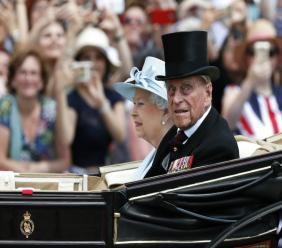 In this Saturday, June 17, 2017 file photo, Britain's Queen Elizabeth II and Prince Philip return to Buckingham Palace in a carriage, after attending the annual Trooping the Colour Ceremony in London. Buckingham Palace said on Wednesday June 21, 2017, Prince Philip is good spirits after being admitted to hospital. (AP Photo/Kirsty Wigglesworth, File)