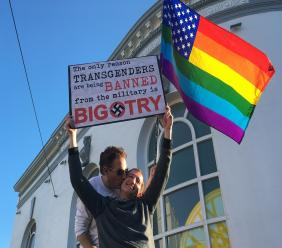 Nick Rondoletto, left, and Doug Thorogood, a couple from San Francisco, wave a rainbow flag and hold a sign against a proposed ban of transgendered people in the military at a protest in the Castro District, Wednesday, July 26, 2017, in San Francisco.