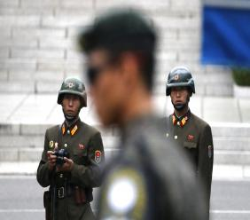 In this April 17, 2017, file photo, two North Korean soldiers look at the south side as a South Korean soldier, center, stands guard while U.S. Vice President Mike Pence visited the border village of Panmunjom which has separated the two Koreas since the Korean War, South Korea. (AP Photo/Lee Jin-man,