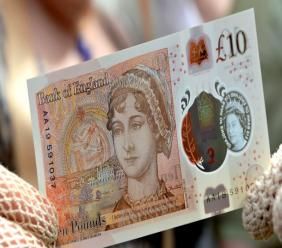 A woman displays the new £10 note featuring Jane Austen, which marks the 200th anniversary of Austen's death, during the unveiling at Winchester Cathedral, England, Tuesday, July 18, 2017.