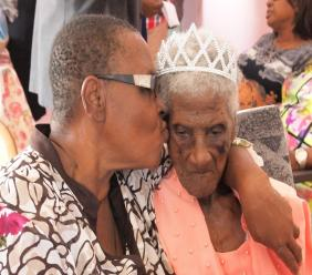 Barbados' lone supercentenarian, Millicent Yearwood receiving a kiss from her only daughter, Mavis Small-Raper, as she celebrated her 110th birthday on July 20.