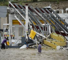 People walk next to a gas station flooded and damaged by the impact of Hurricane Maria, which hit the eastern region of the island, in Humacao, Puerto Rico, Wednesday, September 20, 2017. The strongest hurricane to hit Puerto Rico in more than 80 years destroyed hundreds of homes, knocked out power across the entire island and turned some streets into raging rivers in an onslaught that could plunge the U.S. territory deeper into financial crisis. (AP Photo/Carlos Giusti)