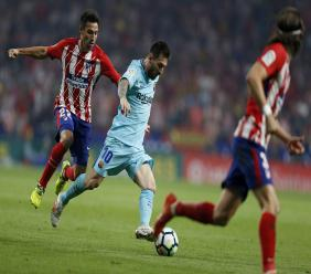 Barcelona's Lionel Messi , centre, sidesteps Atletico Madrid's Nicolas Gaitan during a Spanish La Liga football match at the Metropolitano stadium in Madrid, Saturday, Oct. 14, 2017. The match ended in a 1-1 draw.