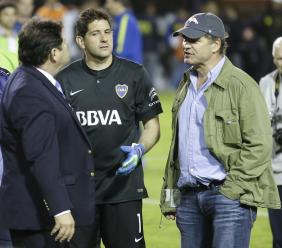 In this May 14, 2015, file photo, CONMEBOL delegate Roger Bello, of Bolivia, left, talks with Boca Juniors goalkeeper Agustin Orion, center, and Alejandro Burzaco, president of Torneos y Competencias, during a Copa Libertadores match between Boca Juniors and River Plate, in Buenos Aires, Argentina. Burzaco, the former CEO of a marketing firm based in Argentina, testified Tuesday, Nov. 14, 2017, at the U.S. trial of three former South American soccer officials accused of taking bribes.