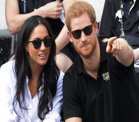 In this Monday, Sept. 25, 2017 file photo, Britain's Prince Harry and his girlfriend Meghan Markle attend the wheelchair tennis competition during the Invictus Games in Toronto. Palace officials announced Monday Nov. 27, 2017, Prince Harry and Meghan Markle are engaged, and will marry in the spring. (Nathan Denette/The Canadian Press via AP, File)