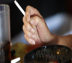 In this April 21, 2015, file photo, a patron smokes a cigarette inside a bar in New Orleans hours before a smoking ban takes effect in bars, gambling halls and many other public places such as hotels, workplaces, private clubs and stores. Cigarette smoking, over-eating and other unhealthy behaviors can be blamed for nearly half of U.S. cancer deaths each year, according to a new American Cancer Society study released Tuesday, Nov. 21, 2017. (AP Photo/Gerald Herbert, File)